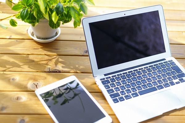 木製の机にノートパソコンやタブレットが置かれている写真