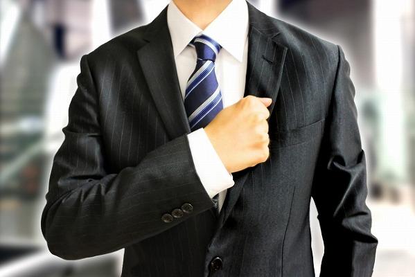 胸に拳をあてているスーツ姿の男性の写真