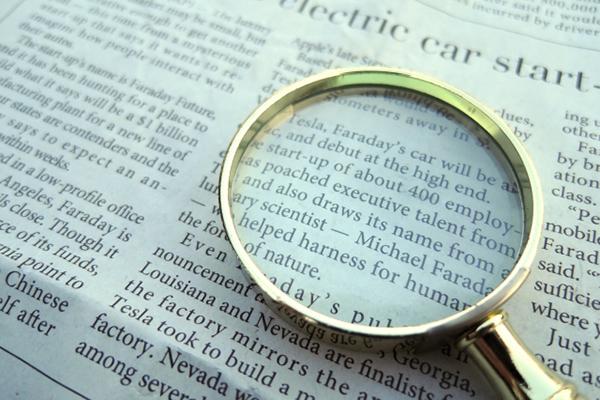 海外新聞と虫メガネの写真