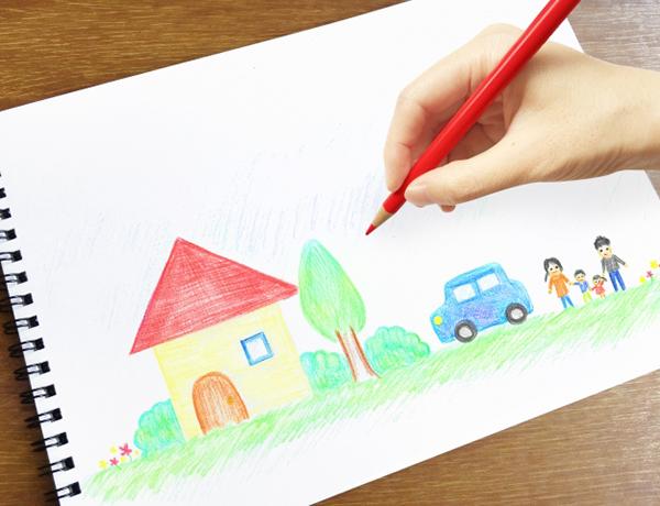 色鉛筆で家や人を描いている写真