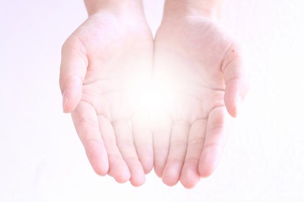 掌で光を包み込んでいる写真