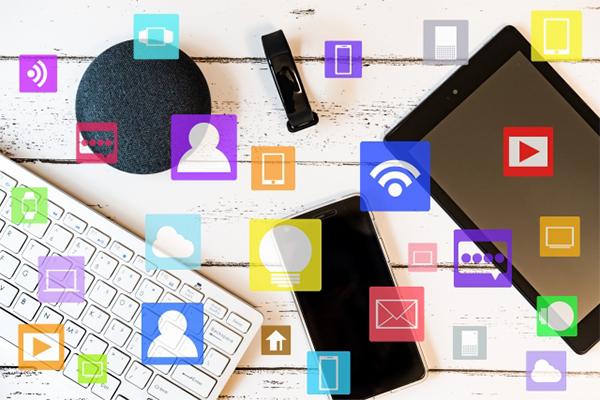スマホやタブレットなどが机に置いてあり、様々なアプリのイラストが描かれている写真