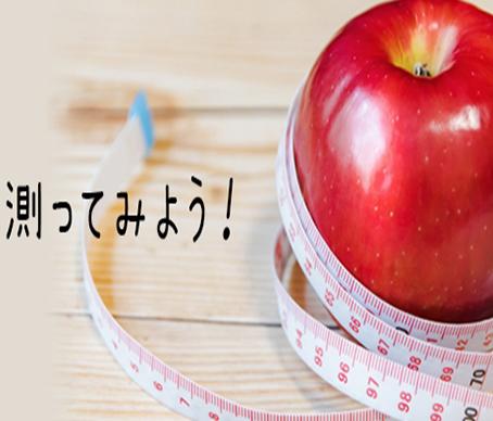 メジャーでりんごを測っている写真