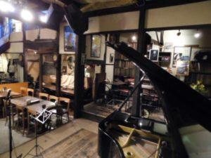 手前にグランドピアノが置かれたステージ、奥はテーブル席 その奥の棚にはレコードが並んでいる