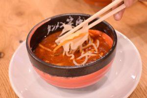 真っ赤なスープに野菜とつけ麺をつけているところ