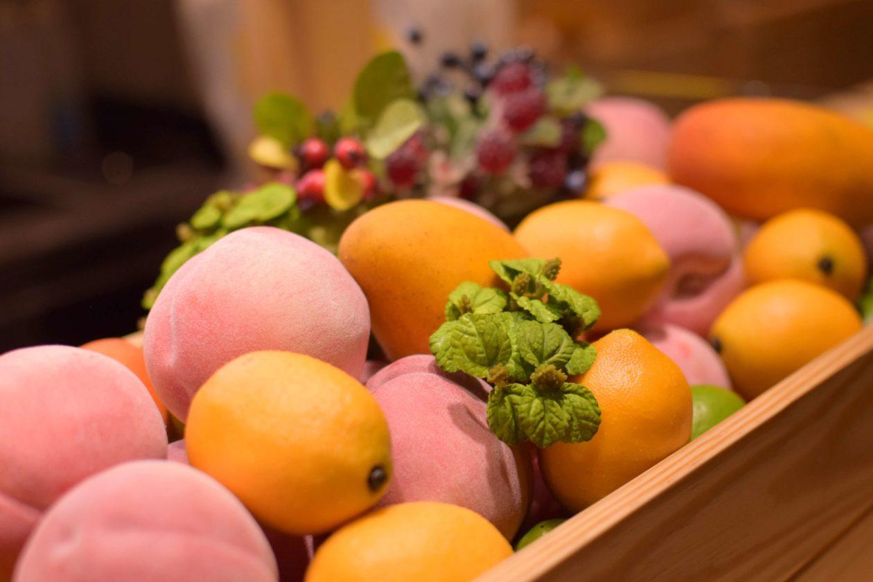 マンゴー、オレンジ、レモン、ラズベリーなどが積み上げてある
