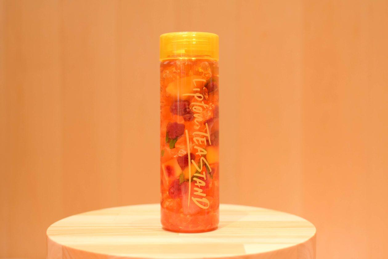 黄色の蓋の透明ボトルにフルーツと氷、紅茶がブレンドされたドリンク。ベリーの赤が鮮やか