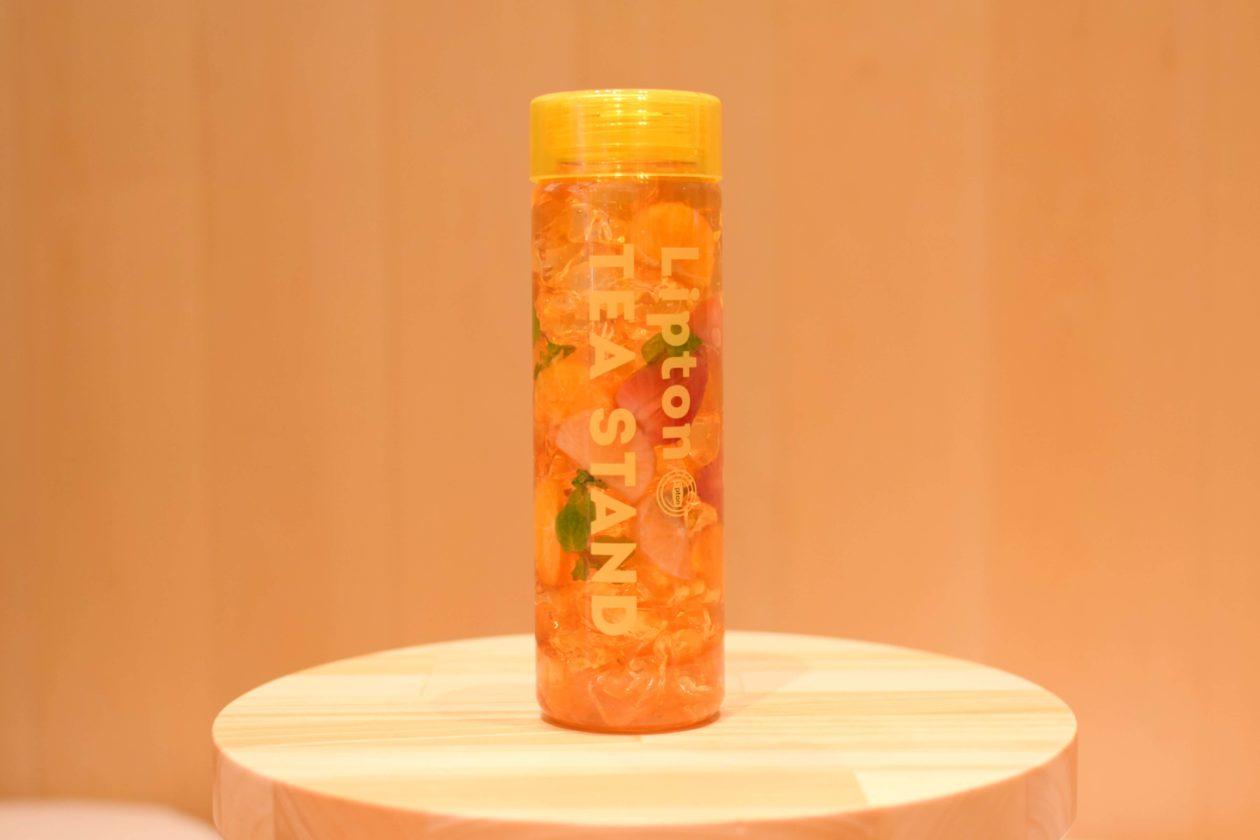 蓋が黄色の透明ボトルにフルーツと氷とコチャがブレンドされたドリンク