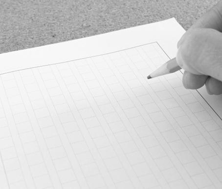 紙の前で鉛筆をにぎっている写真