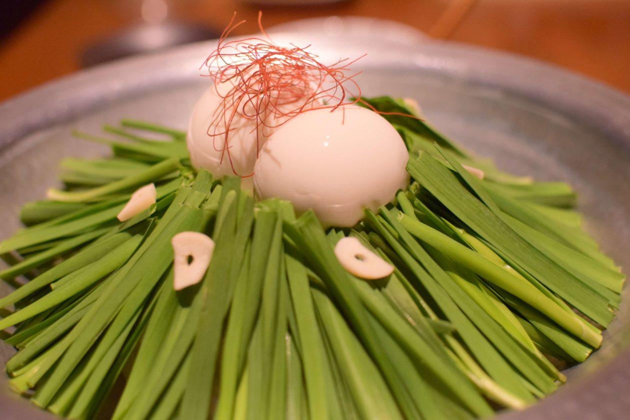 丸い豆腐が真ん中に乗ったニラたっぷりのモツ鍋