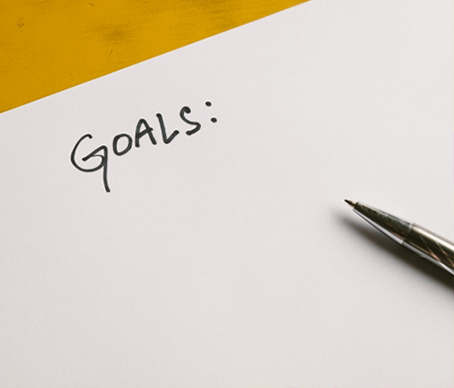 「GOALS」とかかれた紙と紙の上に置かれたペン。