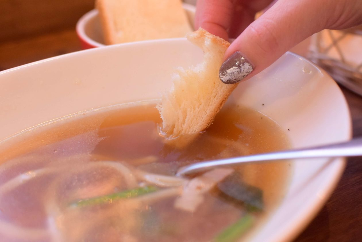 スープにパンをひたしているところ