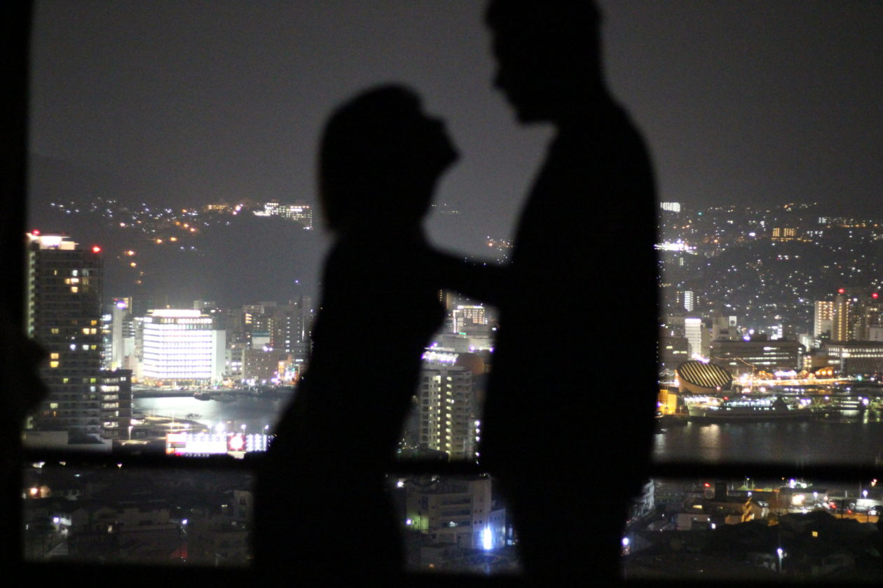 夜景をバックに影絵風で楽しむ二人