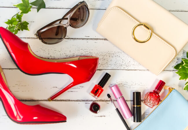 赤い靴やサングラス、ベージュのバックが無造作に並べられてる画像