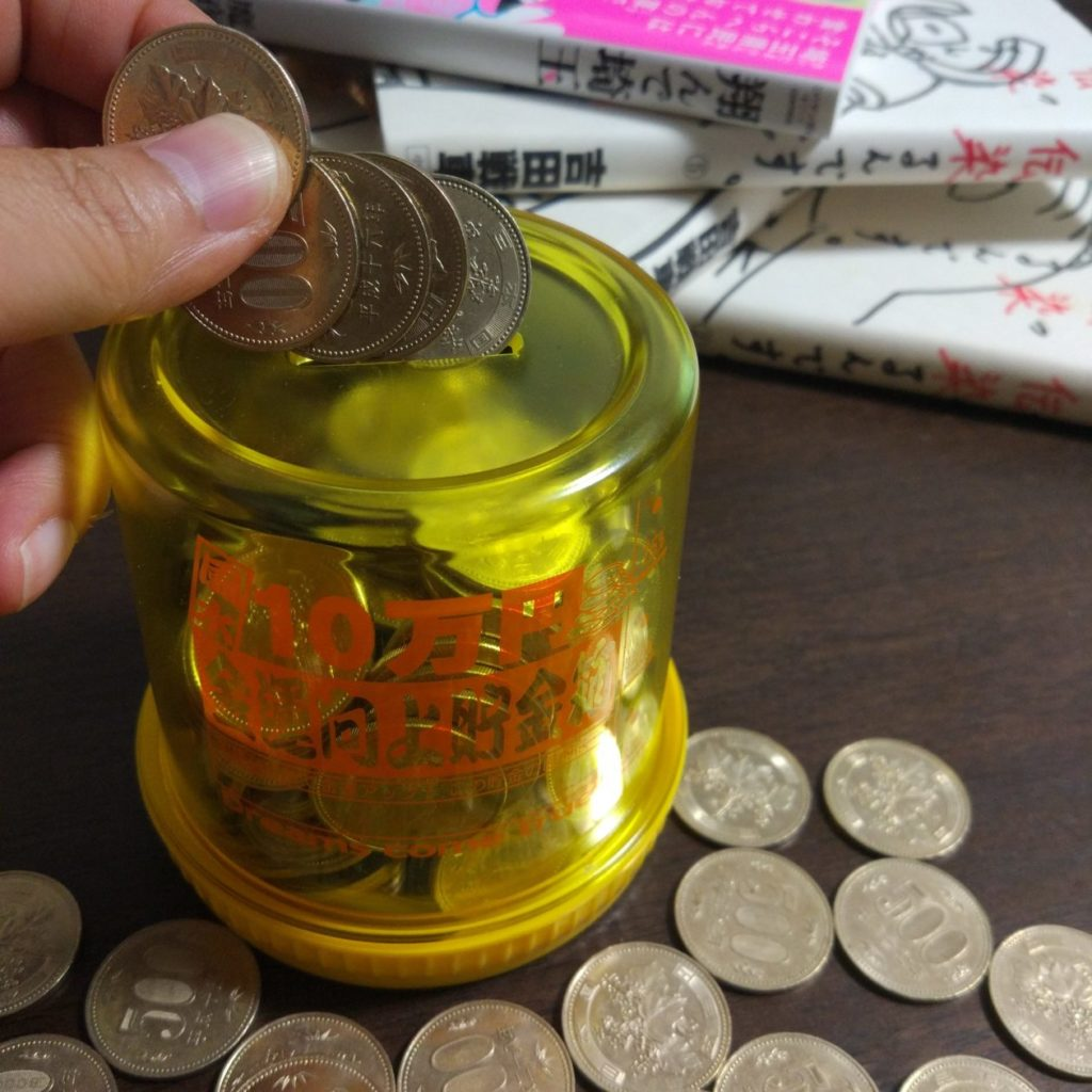 五百円硬貨を貯金箱へ投入