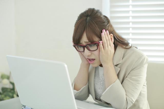 写真:パソコンを見て困っている女性