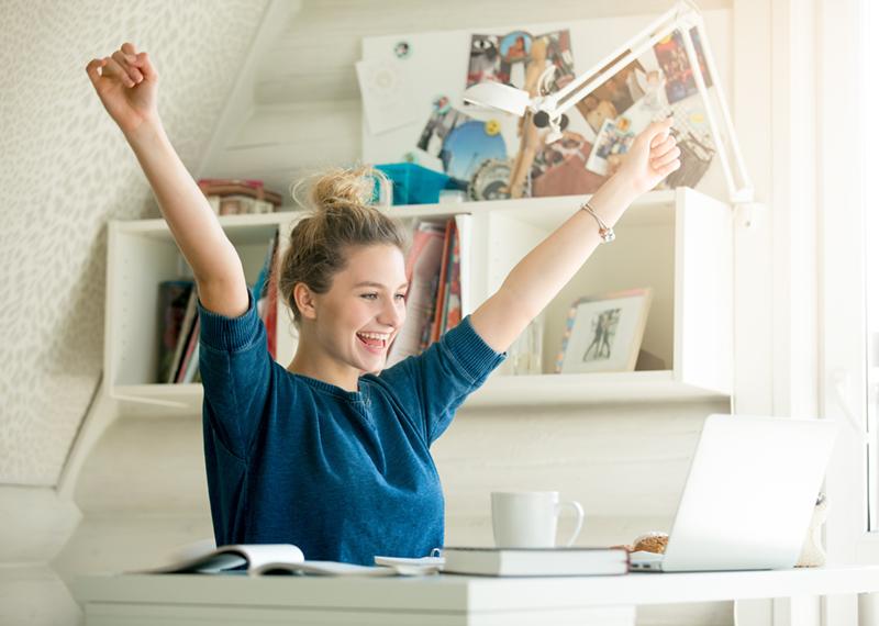 画像:PCを見て喜ぶ女性